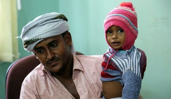 A Yemeni father carries his child suspected of being infected with cholera, as he waits to be seen at a hospital in Hodeidah, Yemen, November 5, 2017.