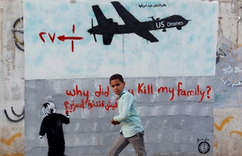 FILE PHOTO: Children in Yemen play in front of graffiti against U.S. drone strikes