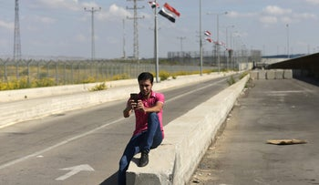 A man takes a selfie at the walking path leading into the Gaza Strip after the Israeli-controlled Erez crossing (background), on November 1, 2017 in Beit Hanun, the northern access point into the coastal Palestinian territory, as the Palestinian Authority takes full control of Gaza's borders. Hamas handed over control of the Gaza Strip's borders with Egypt and Israel to the Palestinian Authority in the first key test of a landmark Palestinian reconciliation accord agreed last month. / AFP PHOTO / MAHMUD HAMS
