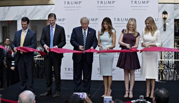 Donald Trump, 2016 Republican presidential nominee, center, cuts a ribbon with his sons Donald Trump Jr., from left, Eric Trump, his wife Melania Trump and his daughters Tiffany Trump and Ivanka Trump during the grand opening ceremony of the Trump International Hotel in Washington, D.C., U.S., on Wednesday, Oct. 26, 2016. The Trump Organization has eight hotels in the U.S. and seven in other countries. The Trump International Hotel Washington, D.C. is housed in the 1899 Romanesque Revival-style Old Post Office on Pennsylvania Avenue. Photographer:
