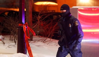 A police officer patrols the perimeter near a mosque after a shooting in Quebec City, January 29, 2017.