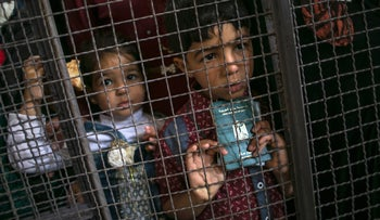 A Palestinian child holds a passport as he waits at the Rafah border crossing with Egypt, in the southern Gaza Strip, after it was opened for two days by Egyptian authorities. May 11, 2016