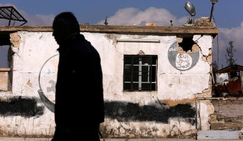 A man walks near a damaged Islamic State sign in government controlled Hanono housing district in Aleppo, Syria December 4, 2016.