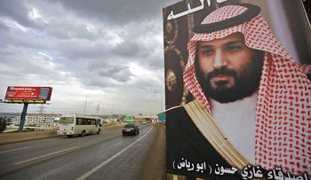 """A poster of Saudi Arabia's Crown Prince Mohammed bin Salman with a phrase reading in Arabic, """" God protect you"""" is seen on a highway in the northern Lebanese port city of Tripoli on November 9, 2017"""
