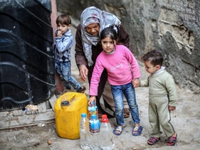 Palestinians filling bottles and jerricans with drinking water at Al-Shati refugee camp in the southern Gaza Strip, on March 22, 2017.
