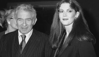 Norman Mailer, left, and his sixth wife, Norris Church. Mailer is wearing a pinstripe suit and a shiny tie. Church is wearing a jacket and earrings and looks taller than him.