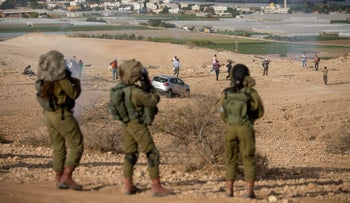 Palestinian and Israeli activists flee tear gas fired by Israeli soldiers during a demonstration against Jewish settlement construction in the West Bank, on November 17, 2016.