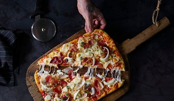 Science shows that men dining with womrn at an all-u-can-eat salad and pizza buffet will eat about twice as much pizza as men who dined with a fellow male. Why? They are showing off their masculinity, suggests the Cornell lab. Shown in picture: A Domino's Pizza chef offering.