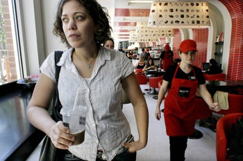 An Israeli woman holds a drink at the Soho branch of Aroma, August 9, 2016.