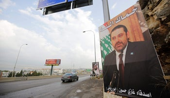 "A poster of Lebanese Prime Minister Saad Hariri hangs on the side of a road with a phrase reading in Arabic, "" God protect you"" in the northern Lebanese port city of Tripoli on November 9, 2017."