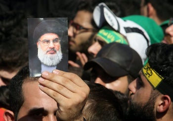 A man holds a photograph of Hezbollah leader Hassan Nasrallah as he speaks to his supporters during the ceremony of Ashura in Beirut, Lebanon, October 1, 2017.
