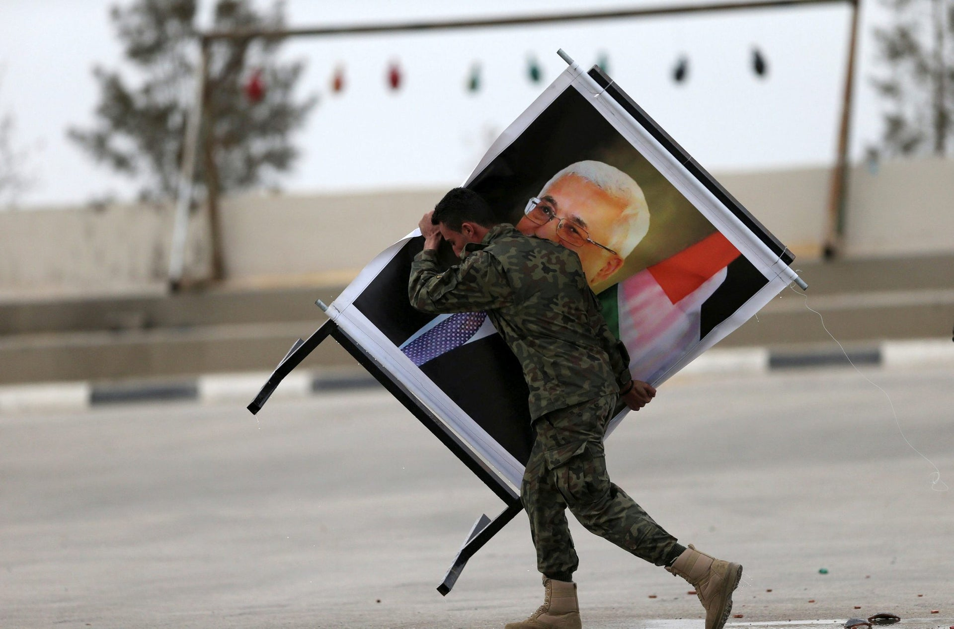A member of Palestinian National Security Forces carries a picture of Palestinian President Mahmoud Abbas during a graduation ceremony for young Palestinians who participated in a military training program, in the West Bank city of Jericho January 25, 2017.