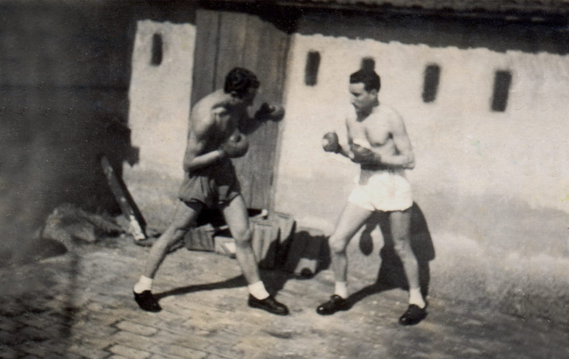 "An undated photo of Pacifico Di Consiglio, better known as ""Moretto,"" left, sparring with a friend, Angelo Di Porto, on the balcony of his home in Rome's Jewish ghetto."