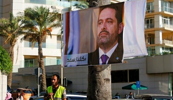 """A worker stands in front of a poster of outgoing Prime Minister Saad Hariri with Arabic words that read, """"We are all Saad,"""", in Beirut, Lebanon on November 11, 2017."""