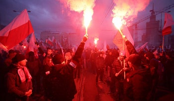 Protesters light flares and carry Polish flags during a rally, organised by far-right, nationalist groups, to mark 99th anniversary of Polish independence in Warsaw, Poland November 11, 2017.