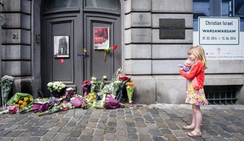A girl stands next to flowers at the Jewish Museum in Brussels the day after a shooting there killed three people, May 25, 2014.