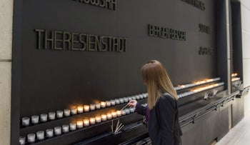 A woman lights a memorial candle during an International Holocaust Remembrance Day Commemoration at the U.S. Holocaust Memorial Museum in Washington, D.C., January 27, 2017.