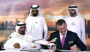 Sheikh Ahmed bin Saeed Al Maktoum (L), CEO & Chairman of Emirates Airline, Kevin Mcallister (R), Executive VP & CEO of Commercial Airplanes Boeing, sign contract during the press conference at Dubai Air Show in Dubai, UAE November 12, 2017