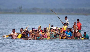 Rohingya Muslims travel on a raft made with plastic containers on which they cross from Myanmar into Bangladesh, Sunday, Nov. 12, 2017.