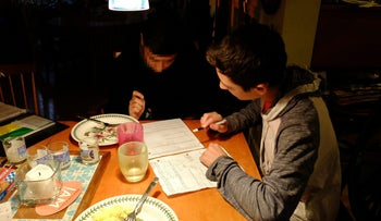 Amir, left, and Noah doing homework. The boys are in the same 10th grade class and often study together.