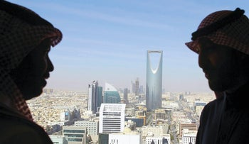 Men look out of a building as the Kingdom Centre Tower is seen in Riyadh, Saudi Arabia, January 1, 2017.