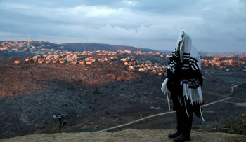 A man covered praying in the outpost of Amona in the West Bank, December 2016.