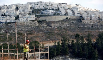 A worker stands in a construction site in the Jewish settlement of Ma'aleh Adumim, West Bank, January 22, 2017.