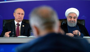 Iranian President Hassan Rouhani, right, and Russian President Vladimir Putin, left, attend a meeting in Tehran, Iran, Wednesday, Nov. 1, 2017. Putin, in Iran on Wednesday for trilateral talks with Tehran and Azerbaijan, offered his support to the Islamic Republic's nuclear deal under threat by President Donald Trump's refusal to re-certify the accord.  (Alexei Druzhinin, Kremlin Pool Photo via AP)