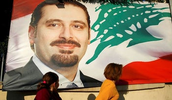 A woman and her daughter pass by a poster of outgoing Prime Minister Saad Hariri, in Beirut, Lebanon, Saturday, Nov. 11, 2017.