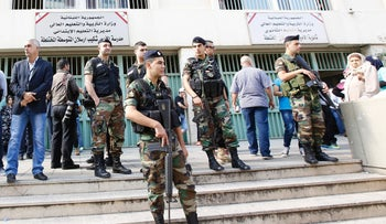 Lebanese security forces stand guard outside a polling station as people head to cast their votes for the municipal elections in Beirut, Lebanon, May 8, 2016.