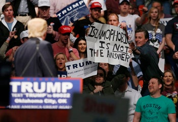 "Donald Trump looks on as a supporter reaches for a sign that reads ""Islamophobia is not the answer"" at a rally in Oklahoma City, February 26, 2016."