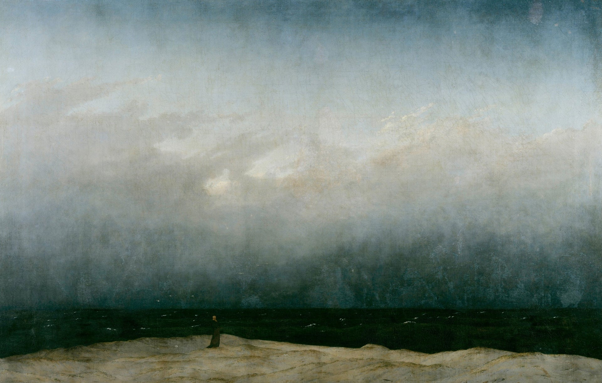 A painting by Caspar David Friedrich titled 'The Monk by the Sea,' showing a dark figure standing on a beach under an overcast sky.