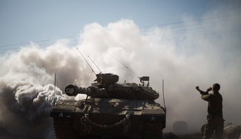 An Israeli soldier directs a tank near the border with Syria in the Israeli-controlled Golan Heights,  Nov. 28, 2016.