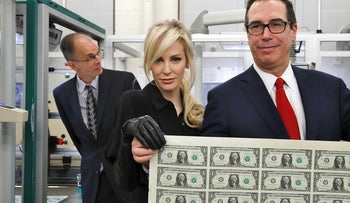 Treasury Secretary Steven Mnuchin, right, and his wife Louise Linton, hold up a sheet of new $1 bills, the first currency notes bearing his and U.S. Treasurer Jovita Carranza's signatures, Wednesday, Nov. 15, 2017
