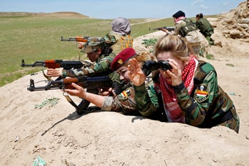 Iraqi Kurdish female fighter Haseba Nauzad and Yazidi female fighter Asema Dahir aim their weapon during a deployment near the frontline of the fight against ISIS, Nawaran, Iraq, April 20, 2016.