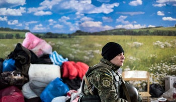 A Ukrainian soldier guards as volunteers prepare a humanitarian aid to distribute to local citizens in Avdiivka, eastern Ukraine, Sunday, Feb. 5, 2017.
