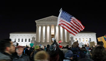 A protester waves an American flag in front of the Supreme Court during a protest about President Donald Trump's recent executive orders in Washington, Jan. 30, 2017.
