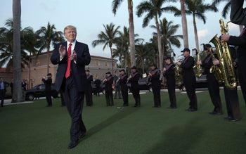 President Donald Trump listens to the Palm Beach Central High School Band as they play at his arrival at Trump International Golf Club in West Palm Beach, Fla., Feb. 5, 2017.
