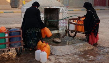 An October 2017 file photo of Moroccan women filling up containers with water from a hose, in Zagora, southeastern Morocco, which has recently seen protests for access to clean water. At least 17 people have died and 40 injured in a stampede on Sunday Nov. 19, 2017 as food aid was being distributed in the village of Sidi Boulalam, in the southern province of Essaouira