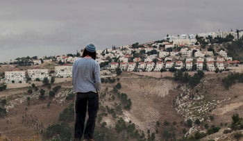 FILE - In this Dec. 5, 2012 file photo, a Jewish settler looks at the West bank settlement of Ma'aleh Adumim, from the E-1 area on the eastern outskirts of Jerusalem.