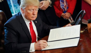 U.S. President Donald Trump signs an executive order in the Oval Office of the White House in Washington, Friday, Feb. 3, 2017.