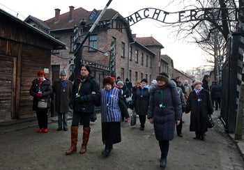 Holocaust survivors walk through the main gate of the Auschwitz Nazi death camp in Oswiecim, Poland, marking the 71st anniversary of its liberation by the Soviet Red Army in 1945. Jan. 27, 2016