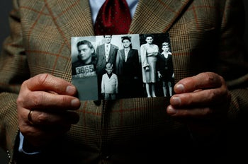 Auschwitz death camp survivor Jacek Nadolny, 77, who was registered with camp number 192685, holds up a wartime photo of his family, as he poses for a portrait in Warsaw. January 7, 2015