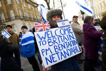 A woman holds a sign welcoming Prime Minister Benjamin Netanyahu to the U.K. ahead of his meeting with British Prime Minister Theresa May in London, February 6, 2017.