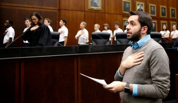 Rohi Atassi, right, from Syria, leads new US citizens in the Pledge of Allegiance after Atassi and 116 others from 37 countries took the oath of citizenship from U.S. District Judge Sara Ellis, left, in the Northern District of Illinois, during a naturalization ceremony Tuesday, Feb. 7, 2017, in Chicago.