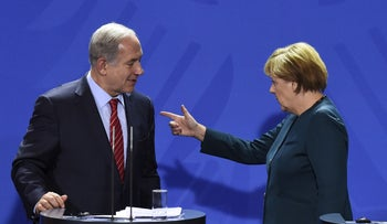 German Chancellor Angela Merkel points the way to Israeli Prime Minister Benjamin Netanyahu (L) after a press conference at the chancellery in Berlin on October 21, 2015.