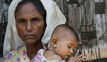 This file photo taken on May 21, 2015 shows an ethnic Rohingya Muslim woman holding a baby at a camp set up outside the city of Sittwe in Myanmar's Rakhine state
