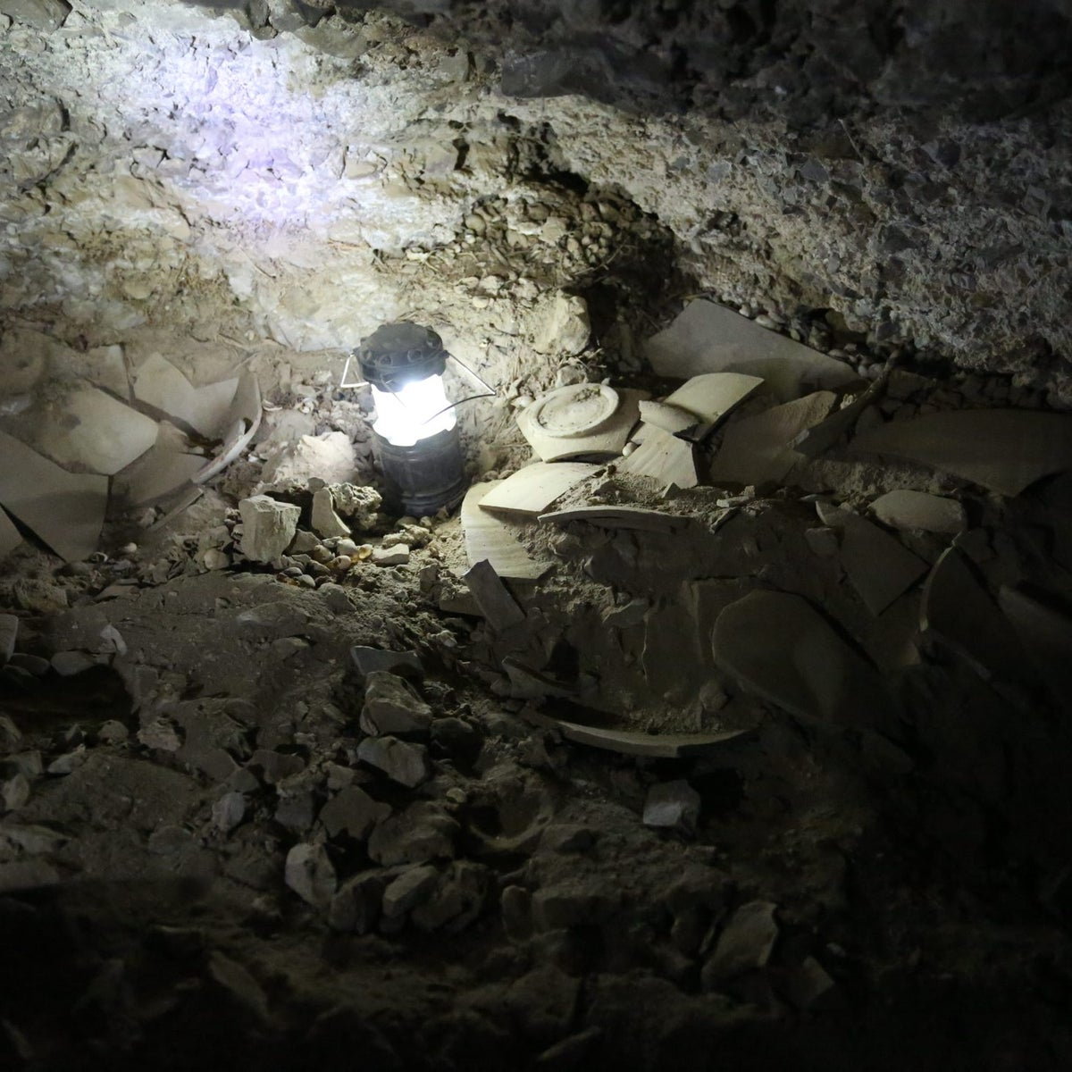 Fragments of jars that contained stolen scrolls, illuminated by a lamp, found deep inside Dead Sea Scrolls Cave 12.