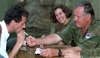 Bosnian Serb wartime general Ratko Mladic (right) lights a cigarette for the head of civilian authorities of the Zepa enclave, east of Sarajevo, Bosnia and Herzegovina, July 27, 1995.