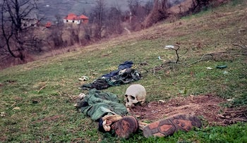 FILE- In this Tuesday, April 2, 1996, file photo, the remains of two bodies and pieces of clothing lie in a field at a suspected mass grave site in the village of Konjevic Polje, approximately 20km (12 miles), north west of Srebrenica. As a U.N court prepares to hand down its verdict in the case against Ratko Mladic, the Bosnian Serb military leader during the Balkan country's 1992-5 war, the remains of numerous victims of genocide and war crimes of which he stands accused still await identification.